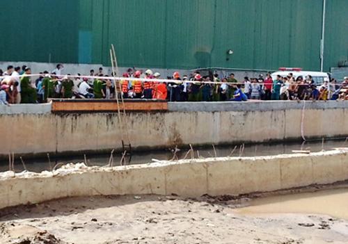 Cảnh sát dùng thang xuống kênh để đưa xác nạn nhân lên bờ. Ảnh: Châu Thành