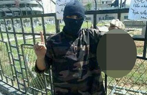 [Caption]Abdel-Majed Abdel Bary, một phiến quân Hồi giáo, chú thích đầy tự hào cạnh bức ảnh đang cầm một chiếc đầu bị chặt đứt của chiến binh đối phương