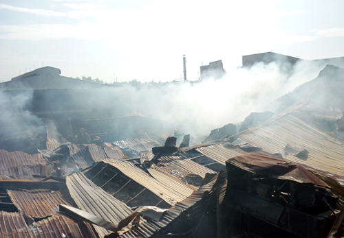 Đến 9h sáng nay, lửa vẫn âm ỉ bên trong xưởng gỗ bị thiêu rụi. Ảnh: An Nhơn