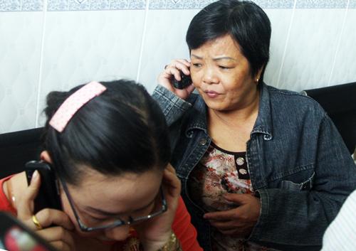 Bà Lan (nghe điện thoại), người sống sót trong căn nhà vì ngủ bên nhà chồng. Ảnh: An Nhơn