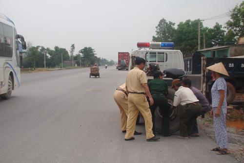 Hình 2: Lực lượng chức năng cùng người dân đang khiêng chiếc bánh này lên xe CSGT. Ảnh: T.L