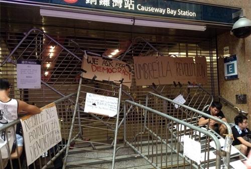 """Xin lỗi vì dựng chướng ngại vật  Một lối vào ga tàu điện ngầm Vịnh Causeway bị chặn lại với những khẩu hiệu đòi dân chủ. Tuy nhiên, người biểu tình cũng không quên để lại tấm bìa carton nhỏ với dòng chữ """"Xin lỗi vì sự bất tiện"""" ở chính giữa. Ảnh: BBC."""