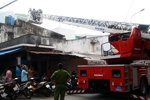 Căn gác gỗ sụp đổ, cảnh sát dùng xe thang để tiếp cận phía trên. Ảnh: An Nhơn