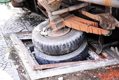 Bánh xe tải sụp xuống hố ga. Ảnh: Châu Thành