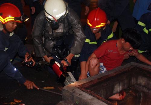 Cảnh sát PCCC quận 3 được điều động tới hiện trường dùng bơm thủy lực, xà beng nâng thành cống thoát nước giải cứu anh Đạt.