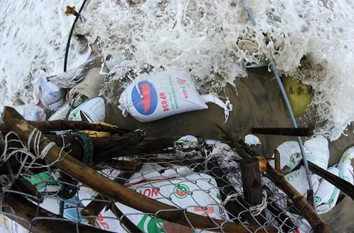 Nhiều nhà hàng ven biển đầu tư thêm lưới thép rào quanh các cọc tre để giữ những bao cát lại, nhưng chỉ sau vài ngày đã bị sóng đánh bung. Ảnh: Nguyễn Đông.