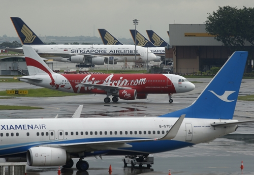 AirAsia's QZ8501 from Surabaya to Singapore, taking the same code as the missing plane which took off 24 hours earlier, taxis at Changi Airport in Singapore December 29, 2014. Indonesia was set to resume at first light the search for an AirAsia plane carrying 162 people from the Indonesian city of Surabaya to Singapore, which went missing on Sunday just after the pilot requested a change in course to avoid bad weather. Singapore said it had sent two naval vessels to help the Indonesian military look for the Airbus A320-200 operated by Indonesia AirAsia, adding a C-130 air force plane took part in the search on Sunday. REUTERS/Edgar Su (SINGAPORE - Tags: TRANSPORT DISASTER)