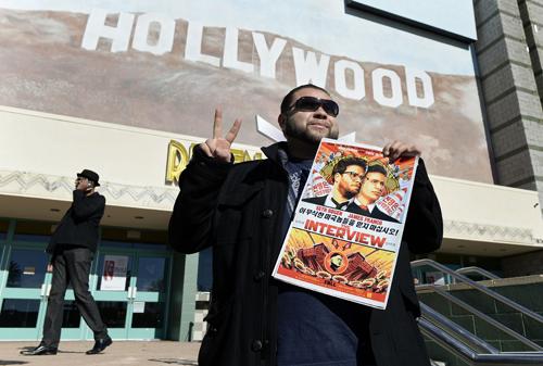 Một khán giả cầm poster phim The Interview trước rạp phim ởLos Angeles, California vào ngày công chiếu 25/12. Ảnh: Reuters