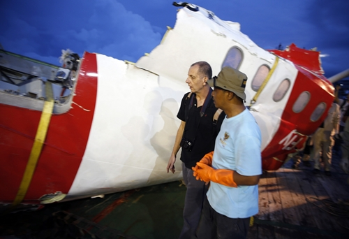 Investigators walk near a section of the tail of AirAsia Flight QZ8501 passenger plane in Kumai Port, near Pangkalan Bun, Central Kalimantan January 11, 2015. Indonesian search teams believe they have found the fuselage of the AirAsia airliner that crashed in the Java Sea two weeks ago, and divers hope calmer waters on Monday will allow them to retrieve the black box flight recorders. REUTERS/Darren Whiteside (INDONESIA - Tags: DISASTER TRANSPORT)