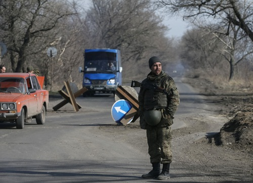 A member of the Ukrainian armed forces stands at the check point near Kurakhovo, not far from Donetsk March 11, 2015. The United States targeted eight Ukrainian separatists and a Russian bank with sanctions and announced more non-lethal aid for Ukraine on Wednesday after accusing Russian-backed rebels of breaking a European-brokered ceasefire. REUTERS/Gleb Garanich (UKRAINE - Tags: POLITICS CIVIL UNREST MILITARY CONFLICT)