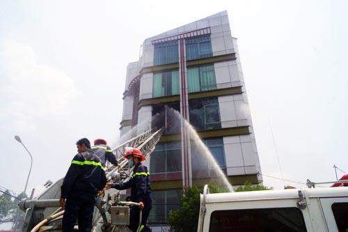 Cảnh sát chữa cháy dùng xe thang dập đám cháy. Ảnh: Nguyệt Triều
