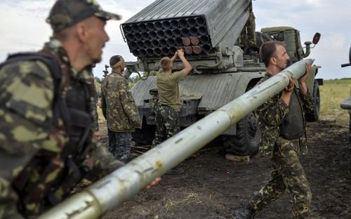 Ukrainian soldiers charge a Grad multiple rocket launcher system, near the eastern Ukrainian city of Shchastya, Lugansk region