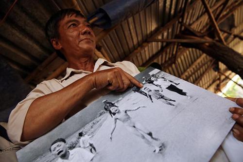 Ông Ho Van Bon chỉ vào bức ảnhchụp cô Phúc và là cậu bé bên trai cô trong bức ảnh năm 1972.Ảnh:AP