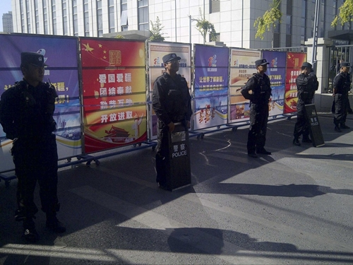 Policemen in riot gear guard a checkpoint on a road near a courthouse where ethnic Uighur academic Ilham Tohti's trial is taking place in Urumqi, Xinjiang Uighur Autonomous Region September 17, 2014