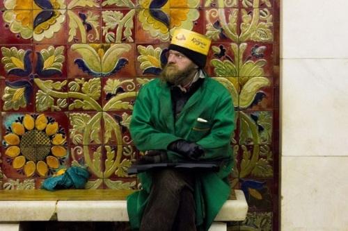 Một người đàn ông đang đội chiếc mũ kì lạ khi đang chờ tàu điện.