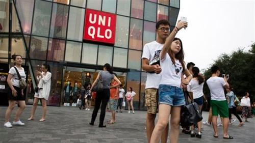 Người Trung Quốc và du khách đổ đến cửa hàngUniqlo chụp ảnh sau vụ việc. Ảnh: AP