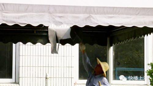 Một công nhân kiểm tra lỗ hổng trên máido tấm kim loại từ máy bay của Air France rơi trúng. Ảnh:Shanghai Daily