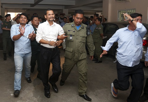Meach Sovannara (center L), a member of the Cambodia National Rescue Party (CNRP), and a supporter of CNRP (L), are escorted by Cambodian police officers at the Phnom Penh Municipal Court, July 21, 2015. A court in Cambodia jailed 11 opposition party members on Tuesday for insurrection after an anti-government protest turned violent a year ago, a verdict that could rock a fragile truce between the country's rival political forces. The 11 Cambodia National Rescue Party (CNRP) members received jail terms ranging from seven to 20 years for forcibly trying to reopen the country's only designated protest venue,