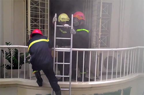 Cảnh sát bắc thang lên tầng trên để tiếp cận dập tắt đám cháy. Ảnh: Hải Thuận.