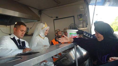 Cô dâu, chú rể tự tay trao đồ ăn cho người tị nạn. Ảnh:Kimse Yok Mu
