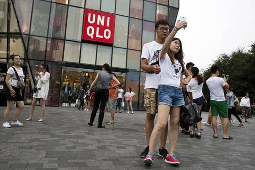 Các nam nữ thanh niên chụp ảnh trước cửa hàngUniqlo tại Bắc Kinh, nơi một cặp đôi quay clip sex trong phòng thử đồ. Ảnh: AP
