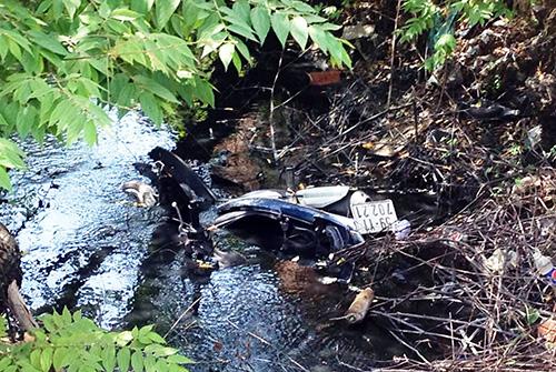 Chiếc xe máy của ba thanh niên nằm dưới mương nước. Ảnh: Hải Thuận.