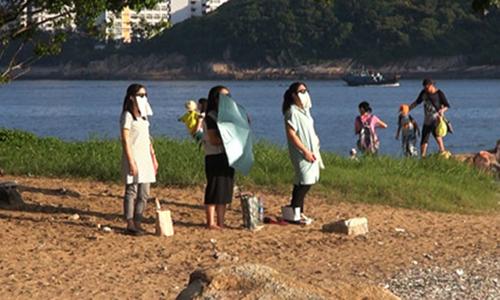 Cáccởi giày và đeo kính râm, hướng thẳng về phía mặt trời. Ảnh:Oriental Daily