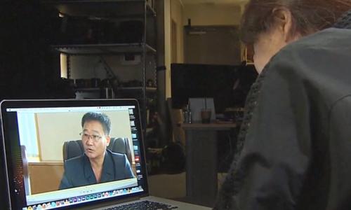 Cô Kim lắng nghe những gửi gắm củachồng và con qua video. Ảnh: CNN