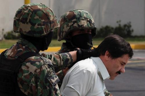 Hai lính thủy quân lục chiến áp giải Joaquin 'El Chapo' Guzman khi trùm ma túy này bị bắt tháng 2/2014. Ảnh: AFP.