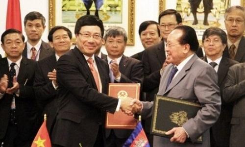 Phó Thủ tướng, Bộ trưởng Ngoại giao Việt Nam Phạm Bình Minh (trái) ký và trao đổi biên bản thỏa thuận của kỳ họp thứ 13 Ủy ban Hỗn hợp Việt Nam - Campuchia về hợp tác kinh tế, văn hóa, khoa học kỹ thuật, với Phó Thủ tướng, Bộ trưởng Ngoại giao và Hợp tác Quốc tế Campuchia Hor Namhong. Ảnh: TTXVN