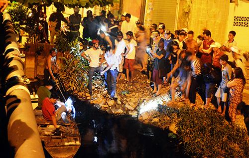 Cảnh sát cùng người dân lùng sục bắt tên trộm dưới kênh nước đen. Ảnh: Hải Hiếu