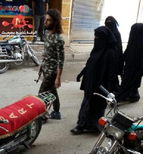 Một chiến binh IS ra đường cùng ba cô vợ trùm kín từ đầu đến chân hôm 6/11/2015. Phụ nữ tại Raqqa bị cấm ra đường một mình. Ảnh: RBSS