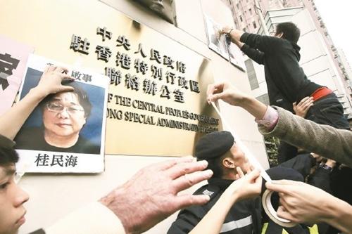 Hình ảnh Gui Minhai (trái), một chủ sở hữu của nhà xuất bản Mighty Current, đang mất tích dán phía trên biển hiệu văn phòng đại diện của Trung Quốc tại Hong Kong ngày 3/1. Ảnh: AFP.