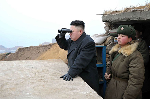[Caption]th Korean leader Kim Jong Un (center) uses binoculars to look at the South's territory from an observation post at the military unit on Jangjae islet, located in the southernmost part of the southwestern sector of North Korea's border with South Korea. (Associated Press/KCNA via KNS) **FILE**