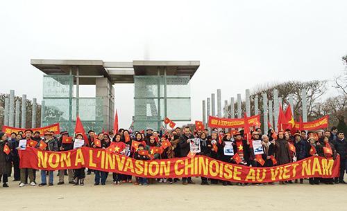"""Cộng đồng người Việt cầm băng rôn lớn có dòng chữ """"Phản đối Trung Quốc bành trướng"""" tại Quảng trường Joffre,thủ đô Paris, v"""