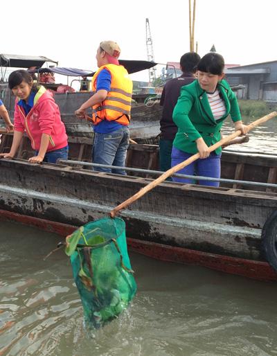 Việc vớt rác và tuyên truyền nâng cáo ý thức bảo vệ môi trường thường xuyên tại chợ nổi Cái Răng. Ảnh: Cửu Long