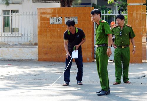 Cảnh sát khám nghiệm hiện trường vụ án mạng trước cổng trường. Ảnh: Huỳnh Tư