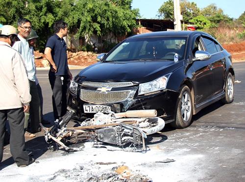 Chiếc xe máy nằm trước đầu ô tô bị cháy trơ khung. Ảnh: Kh.uyên