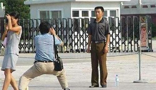 Trong khi người mẫu tạo dáng nghiêm túc, nhiếp ảnh gia có vẻ phải khổ sở 'đứng tấn'.