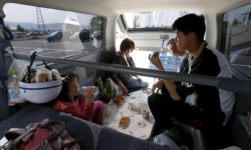 Một gia đình sống sót sau động đất phải dùng ôtô làm nơi trú ẩn tạm thời. Ảnh: Reuters