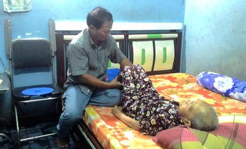Ông Nguyễn Văn Tấn bên cạnh giường bệnh của mẹ.