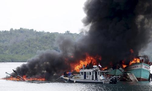 Tàu cá Việt Nam và Malaysia bị Indonesia phá hủy với cáo buộc đánh bắt cá trái phép ngày 5/4. Ảnh: Reuters.