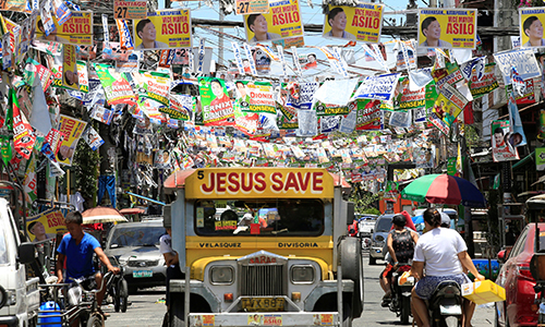 [Caption]Election posters of Philippine candidates are seen hanging above a jeepney driving along a main street in Pritil, Tondo city, metro Manila in the Philippines May 8, 2016, ahead of the election on Monday. REUTERS/Romeo Ranoco