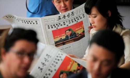 Phóng viên nước ngoài và hướng dẫn viên Triều Tiên đọc báo trong dịp đưa tin về Đại hội đảng Lao động Triều Tiên. Ảnh: Reuters