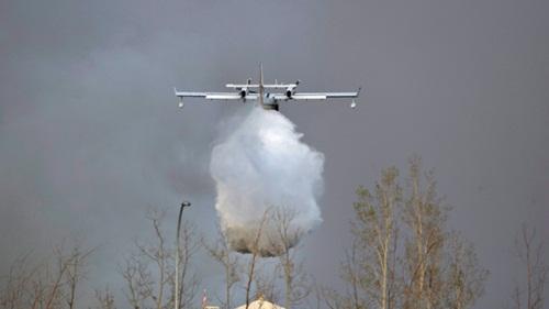 Máy bay chữa cháy thả bom nước xuống đám cháy rừng ở Alberta. Ảnh: