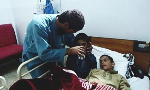 Người cha đang chăm sóc cho hai cậu bé vào lúc tối, khi hai bé không thể nói chuyện, ăn uống. Ảnh: odditycentral