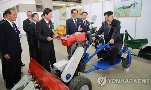 Ông Kim Jong-un ngồi trên chiếc máy cày do Triều Tiên sản xuất. Ảnh: Yonhap