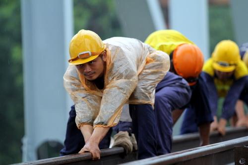 Để hoàn thành cầu sớm hơn tiến độ, công nhân làm trong mưa ngày 25/6. Ảnh: Phước Tuấn