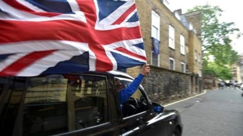 Tài xế taxi cầm cờ Anh. Ảnh: BBC