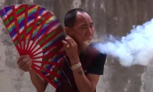Võ sư Lưu Phi biểu diễn khả năng tạo ra khói, lửa bằng mùn cưa lèn chặt trong miệng. Ảnh: Mirror.